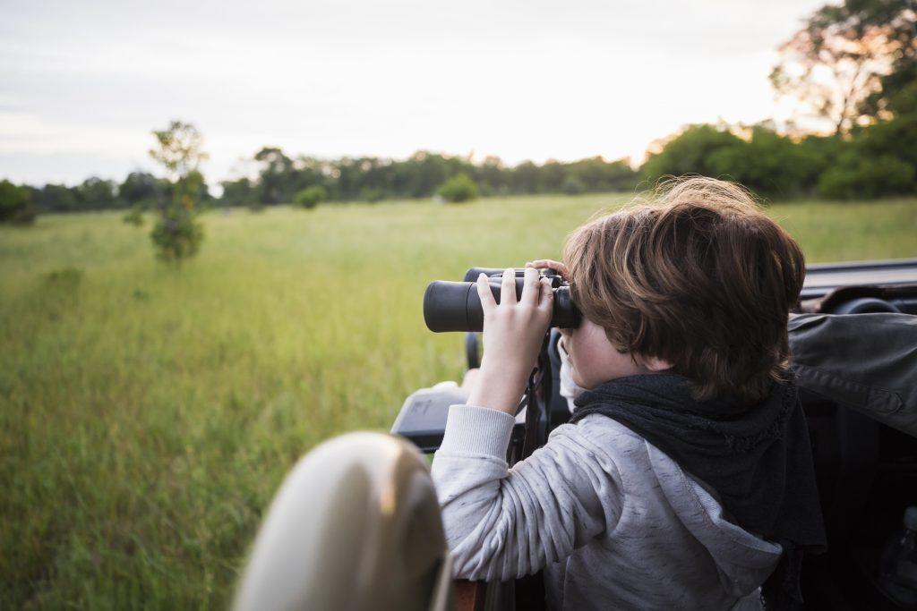 Botswana,A six year old boy using binoculars seated in a safari jeep.