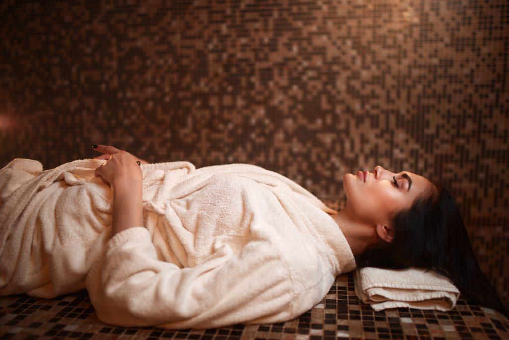 Woman lying on a hot stone, turkish hamam, sauna
